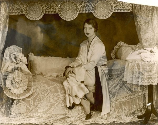 Woman in court shoes & silk two-tone lounging pyjamas with belted wrap over jacket & cropped trousers with bell- shaped scallop edged cuffs sits on a lacy bed