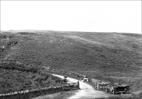 A typical countryside scene in Devon, with a narrow country lane winding through a hillside. An open-topped Chevrolet car is parked to the right of an open five-bar gate. Photograph by Ralph Ponsonby Watts