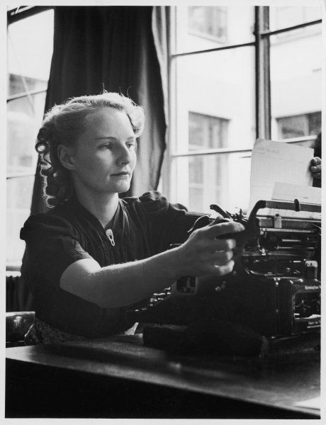 A blonde typist rolls the paper up out of the typewriter as she checks a letter for errors
