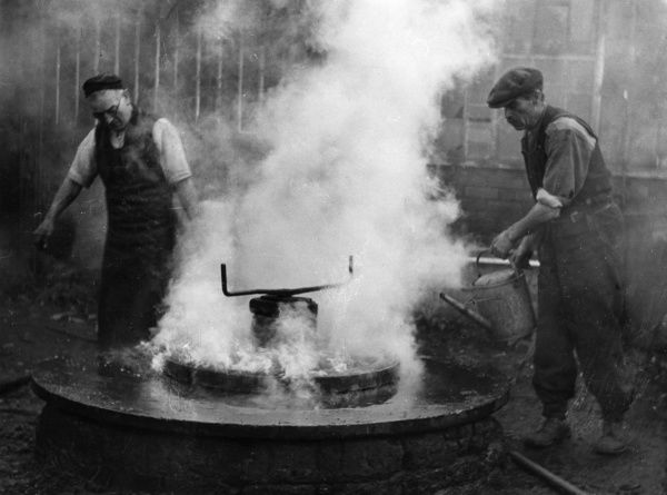 Wheelwrights tyring a wheel the old-fashioned way, Berkshire, England. Date: 1930s