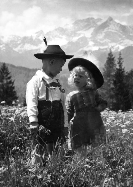 Two children in Tyrolean costume, standing in a field of flowers, with the Alps behind them. Date: 1930s