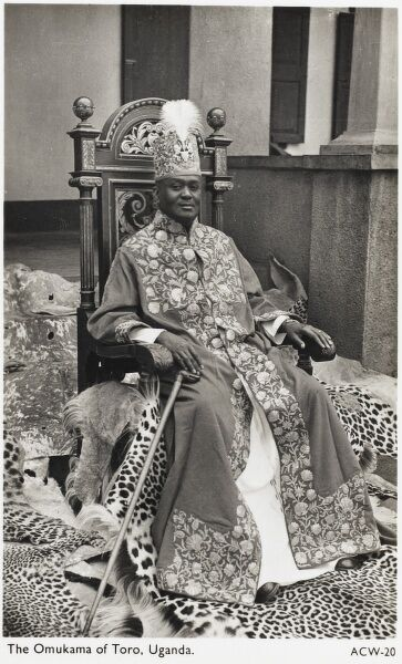 Uganda - Tribal King Rukidi III (ruled 1929 - 1965) - seated in his opulent throne, surrounded by leopard and cheetah skins and wearing a hat with an Osprey feather