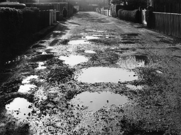 Potholes and puddles in an unadopted road. Date: 1960s