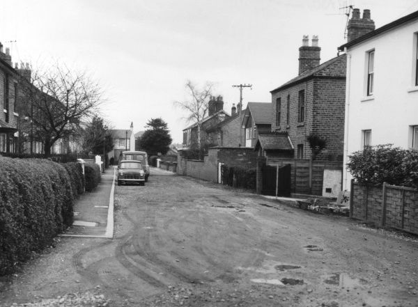 A private (unadopted) road, supposedly maintained by the owners of the houses, but full of potholes! Chester, Cheshire, England. Date: 1960s