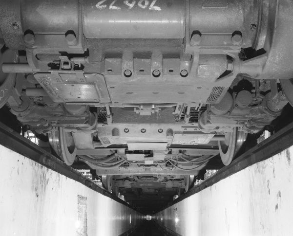 The bootm of a train carriage viewed from the bottom of a pit in a railway shed, cut out of the floor to allow engineers to access the undercarriage for repairs and adjustments. Photograph by Heinz Zinram