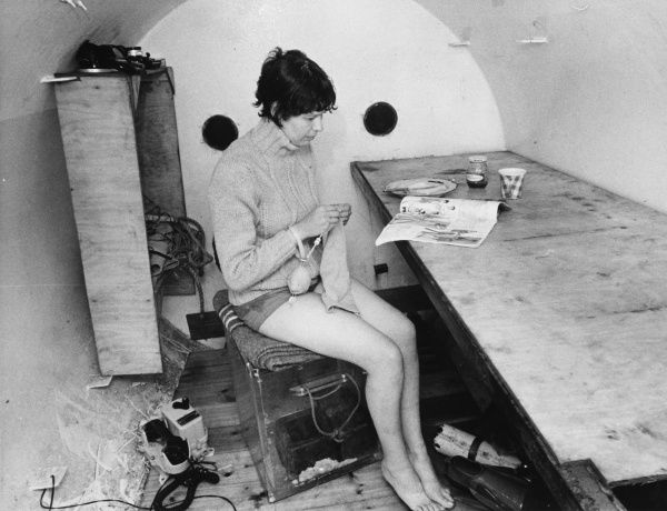 A female physicist, 'multi- tasking' (reading a magazine whilst knitting!) in 'Sealab II', Britain's first permanent underwater laboratory, off the coast of Plymouth, Devon. Date: 1960s