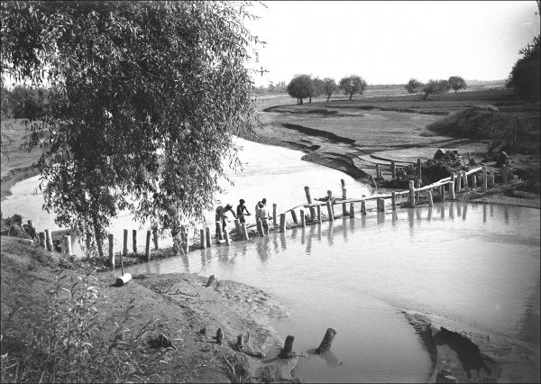 Unidentified location, possibly in the Middle East, showing a river and a primitive bridge. Photograph by Ralph Ponsonby Watts