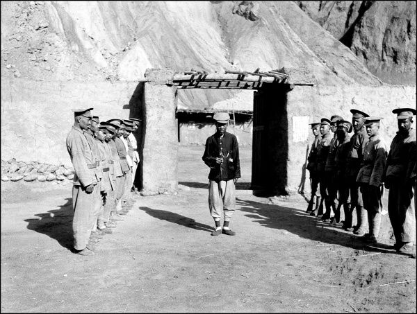 A group of uniformed men in the mountains of Kashgar, western China. They are lined up in two rows, with one man at the centre, with a square archway behind him. Photograph by Ralph Ponsonby Watts