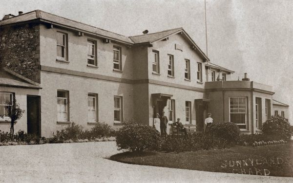 The Chard Union workhouse, also known locally as Sunnylands, in Chard, Somerset. The people in front are presumably the master and matron (right) and porter and nurse (left). The building, designed by George Wilkinson, was erected in 1836-8