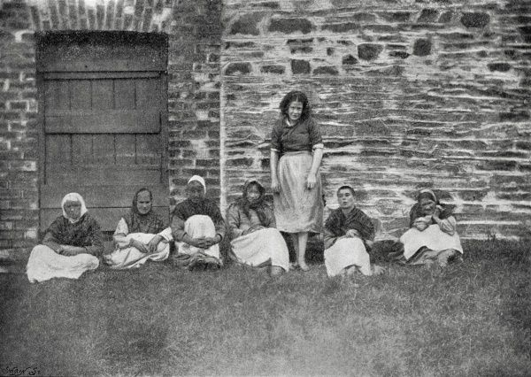 Female lunatic inmates sit in an airing yard at the Cootehill Union Workhouse, County Cavan, Ireland