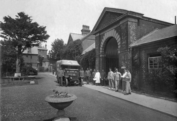 The entrance to the Guildford Union workhouse, Surrey, during its First World War deployment as a military hospital. Various military personnel can be seen, including an officer on crutches. A Red Cross ambulance stands alongside. The building