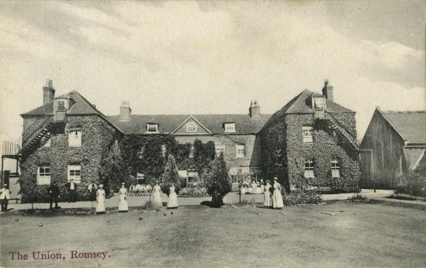 The Union workhouse on Winchester Road, Romsey, Hampshire. Some of the workhouse staff appear to be playing croquet while workhouse inmates are seated on benches behind. The building, originally the Romsey parish workhouse dating from 1774, was taken over