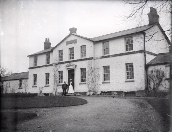 Main entrance of the union workhouse, opened in 1838 at South Molton, Devon. A man and woman, presumably the master and matron, stand at the doorway