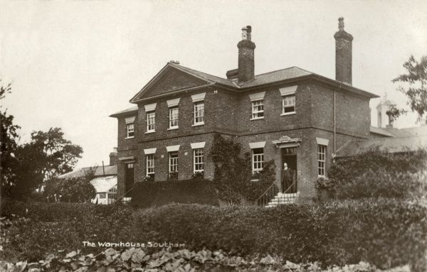 The Southam Union workhouse on Welsh Road in Southam, Warwickshire. A man, perhaps the workhouse porter, stands on the doorstep. A greenhouse is attached at the left of the building. Designed by John Plowman, the workhouse was erected in 1837
