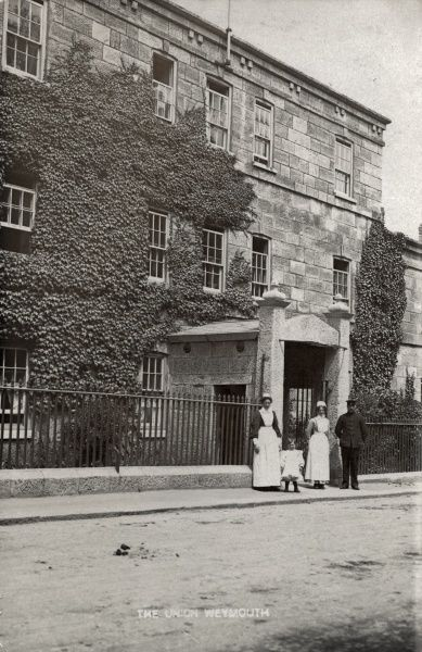 The porter and uniformed female staff stand at the entrance to the Weymouth Union workhouse, erected in 1836 on Wyke Road, Weymouth, Dorset. The building later became Portway Hospital but has now been converted to residential use