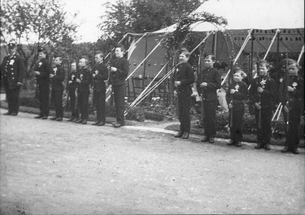 A line of boys at Tonbridge Union workhouse in Kent, probably in band uniforms, hold their rifles in military drill style