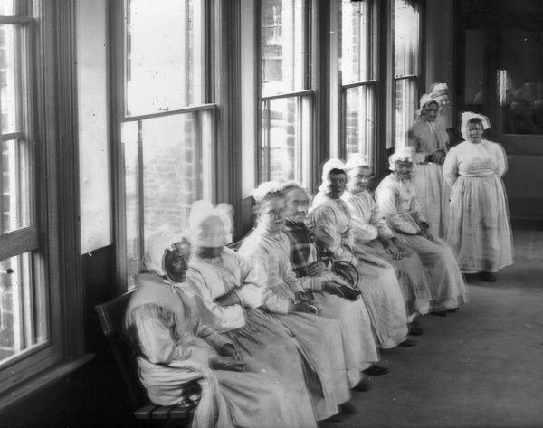 A row of female inmates seated by a window inside the Tonbridge Union workhouse. A uniform of long skirt, blouse, shawl and bonnet was the normal attire for elderly women in the workhouse. Some of the women have moved during the exposure of the photograph