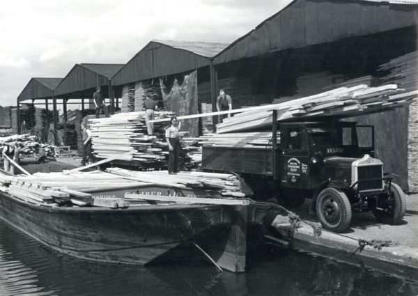 Unloading timber from barges, an unfamiliar London scene, near the Surrey Docks. Date: 1930s