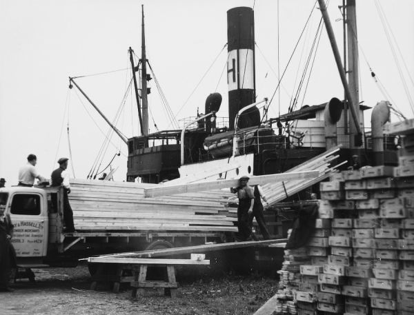Workmen unloading a timber boat at Bristol docks, Gloucestershire, England