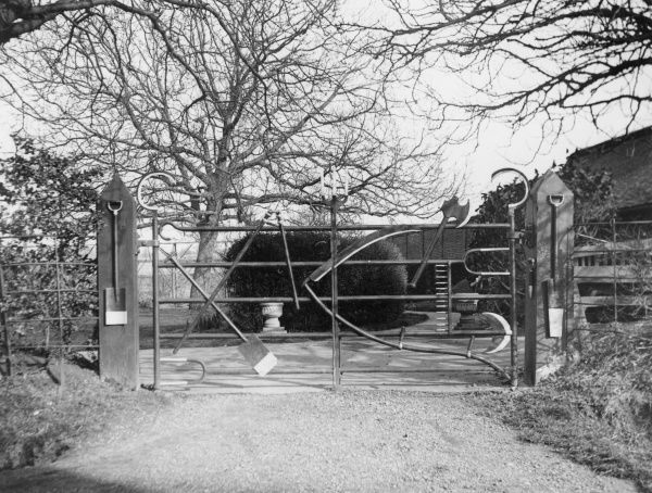 An unusual farm gate, with a spade, scythe, axe etc, incorporated into its design, near Tring, Hertfordshire, England. Date: March 1939