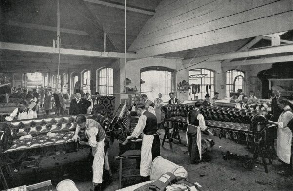Upholsterers at work at Mr C V Smith's factory in Osnaburgh Street, Camden, London. Teams of men are assembling and stuffing long leather couches