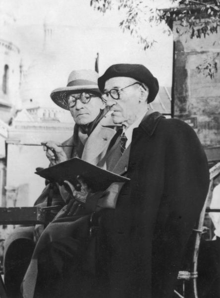 "MAURICE UTRILLO French painter, best known for his Parisian street scenes, with the actor and dramatist SACHA GUITRY (1885-1957), in Montmartre, Paris, 1955. Utrillo is painting a canvas for film ""If Paris Were Told to Us&quot"