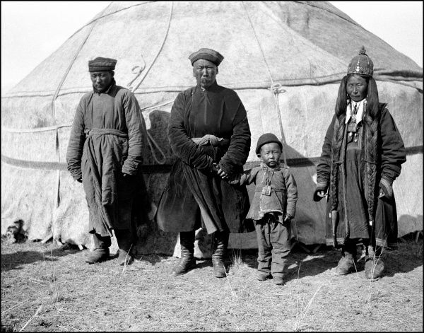 A Uyghur family stand before their traditional tent house - Xinjiang Province, southern China. Photograph by Ralph Ponsonby Watts during his journey from Kashmir to Kashgar