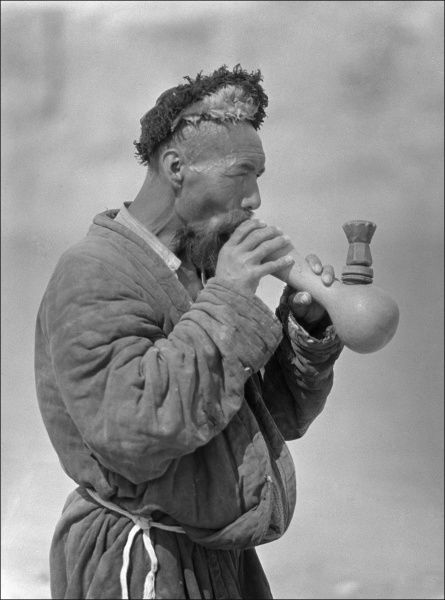 A Uyghur man smoking an elaborate pipe. Photograph by Ralph Ponsonby Watts