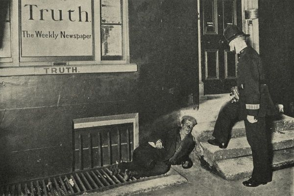 A policeman shines his torch down on a vagrant asleep on the pavement outside the offices of the 'Truth' weekly newspaper