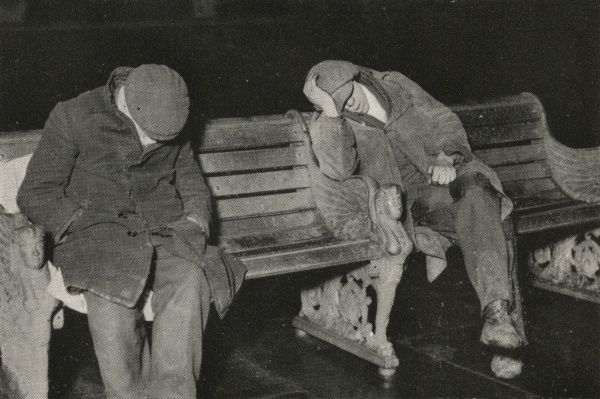 Two tramps in shabby overcoats, flat caps and muddy shoes, spend the night on a bench on London's Thames Embankment