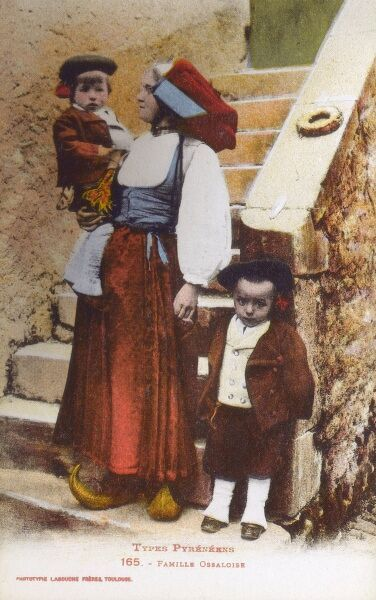 Family from Val d'Ossau consisting of a Mother and her two young sons. One of the boy's rattles has been left on the steps, perhaps that is the cause of his slightly distressed expression ?! Date: circa 1910s