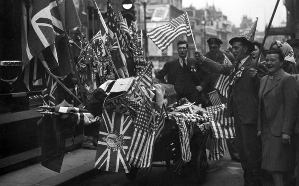 A flag seller does a roaring trade offering Allied flags for sale during the VE Day celebrations in London on 8th May 1945. At least we think he's a flag seller - it could possibly be a cart heavily adorned in flags!