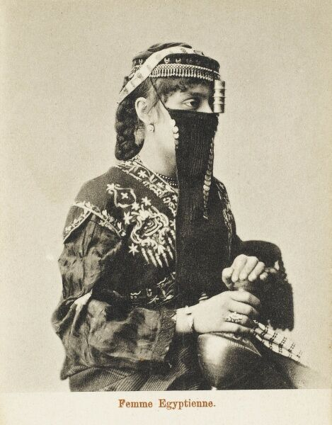 A fine portrait of an Egyptian woman, wearing a very elaborate veil and a small tassled round hat, decorated with crescent moons. She holds an interestingly shaped ceramic vessel in her lap