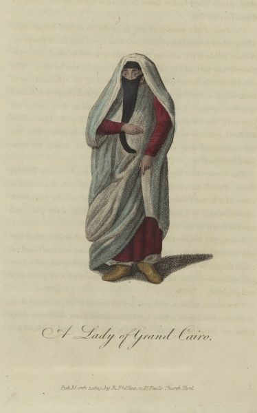 A Lady of Grand Cairo, Egypt. An Egyptian woman in a white robe with a veil across her face