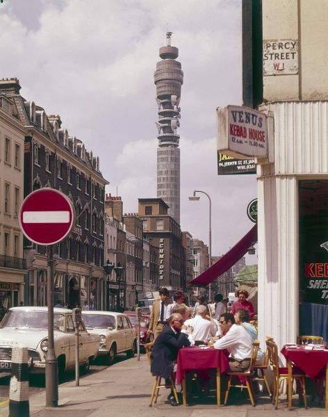 Dining outside the 'Venus Kebab House' on the corner of Percy Street, central London, with the Post Office Tower behind. Date: 1969