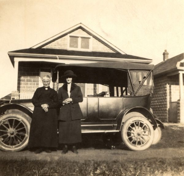 A vicar and his wife pose alongside their soft-top moteor, possible an Austin