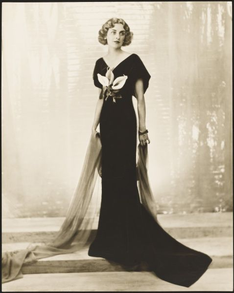Photograph of Agness Rafelle, Duchess of Leinster wearing a stunning black bias cut evening gown by Victor Stiebel, trimmed with arum lilies