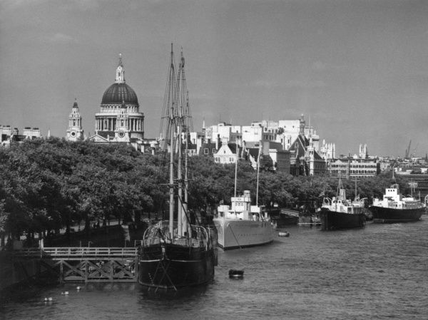 The Victoria Embankment, central London, with boats moored along the River Thames and the dome of St. Paul's Cathedral on the horizon. Date: 1950s