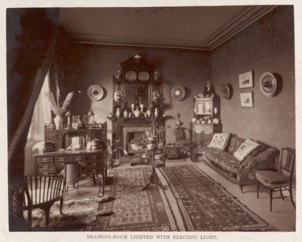 A Victorian sitting room with electric light on the walls