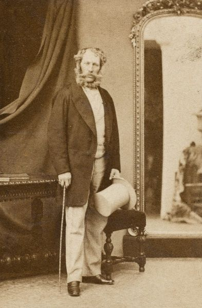 A Victorian man standing by a mirror. It is probably Frederick Charles Polhill-Turner (1826-1881), around the time of his wedding to Emily Frances Barron in 1852. He became a Justice of the Peace, Deputy Lieutenant, High Sheriff for Bedfordshire in 1855