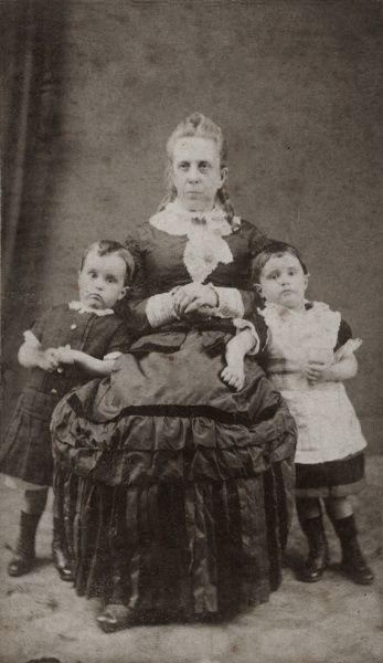 A middle aged Victorian woman poses with two children in the photographer's studio. She has a rather serious expression on her face, and the children look bored. Date: late 19th century