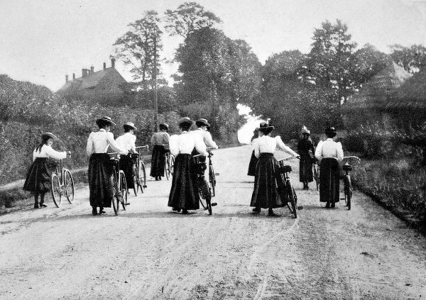 Photograph showing a group of women pushing their bicycles up a hill; probably somewhere in England in the summer of 1897