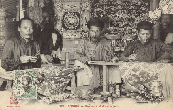 Embroiderers and draughtsmen at work in a textile workshop in Hanoi, Vietnam, surrounded by the glorious results of their labours. Date: circa 1903