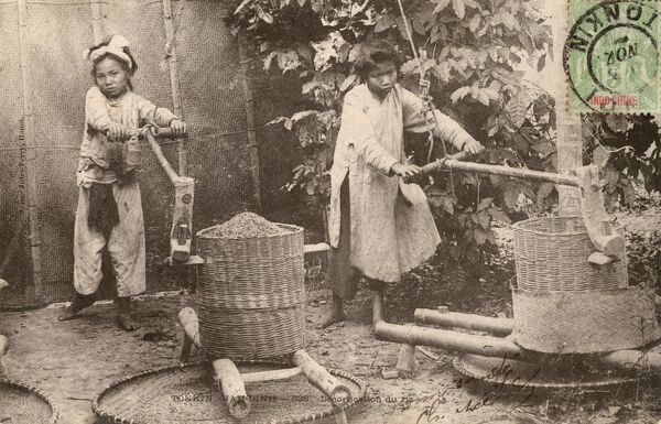 Two young girls working at the 'decortication' (husking/hulling) of rice in Hanoi, Vietnam. Date: circa 1903