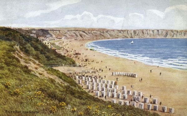 View of the beach at Filey Bay, North Yorkshire, from the south, with bathing huts set out in rows. Date: circa 1920