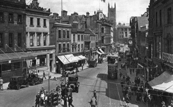 View of the Cornmarket, in the centre of Derby, busy with shoppers, trams and cars. The tower of the Cathedral can be seen in the middle distance. Date: circa 1920