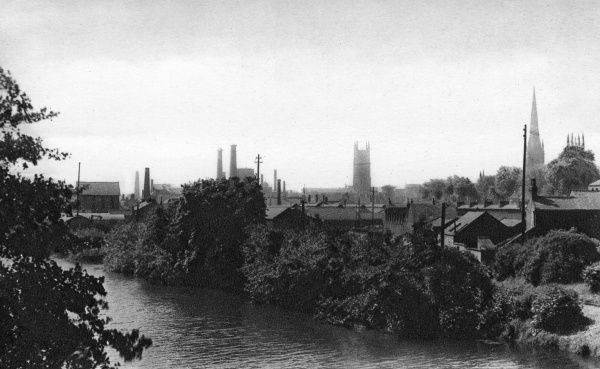 A view of Derby from across the River Derwent, showing a mixture of church towers and spires, and factory chimneys. Date: circa 1910