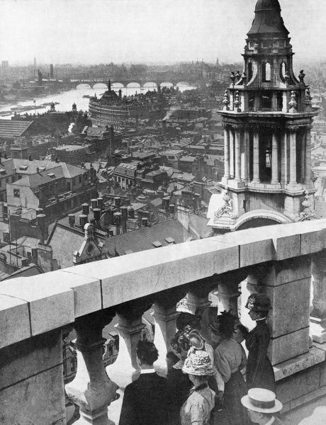 Visitors to St. Paul's Cathedral in the City of London look across London from its roof towards the River Thames and Westminster Abbey. Date: 1911