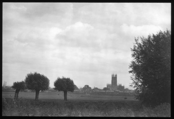 A typical view across English fields, with a cathedral (possibly Worcester Cathedral) on the near horizon, surrounded by houses