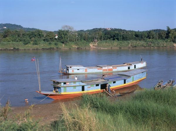View across the Mekong River at Chiang Khong, Thailand, with Laos in the distance, and river boats on the near bank
